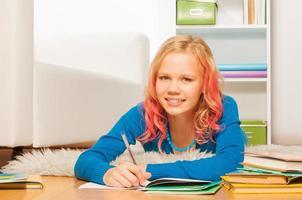 slim geweest blond meisje huiswerk op de thuisvloer foto