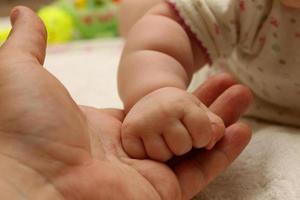 de hand van het kind houdt een hand van de volwassene vast foto