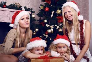 kleine meisjes met hun moeders poseren naast een kerstboom