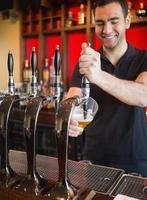 knappe barkeeper die een pint bier trekt foto
