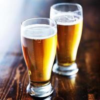 twee mokken amberkleurig bier foto