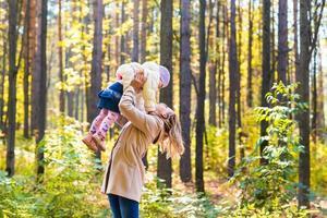 gelukkige familie moeder en dochtertje spelen op herfstwandeling foto