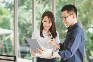 Aziatische zakenman en vrouw die nieuw zakelijk project bespreken