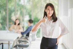 Aziatische zakenvrouw lachend met thumbs up gebaar