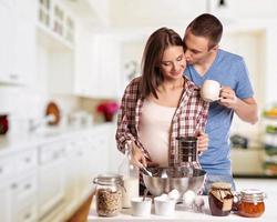 vriendin terwijl ze brood snijdt voor het ontbijt in de keuken foto