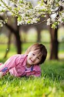 schattig gelukkig kind buiten op de lentedag in een prachtige bloei