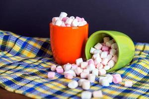 marshmallows morsen uit een groene beker