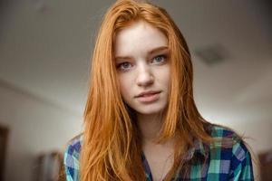 portret van doordachte aantrekkelijke roodharige jonge vrouw in geruite overhemd foto