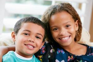 twee jonge broers en zussen zittend op een bank en knuffelen foto