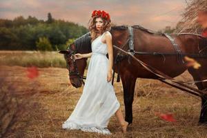 meisje loopt het veld in met een val van een paard. foto