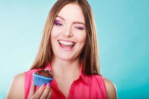 lachende vrouw houdt chocoladetaart in de hand