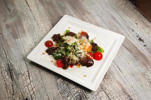 Caesar salade met vlees, tomaten en geraspte Parmezaanse kaas foto