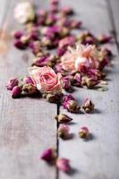 gedroogde rozenknoppen verspreid over een houten tafel