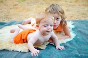 babyjongen buitenshuis met zijn zus foto