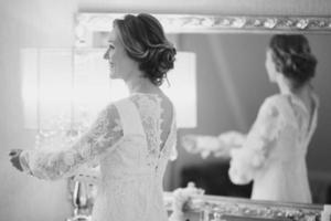 zwart-wit trouwfoto van een bruid die zich klaarmaakt. foto