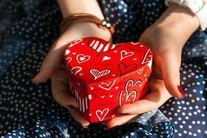 doos in vorm van hart in vrouwelijke handen foto