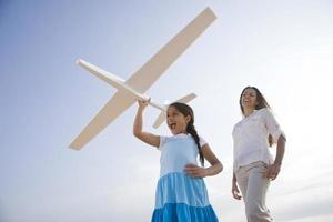 moeder en dochter met plezier met speelgoedvliegtuig foto