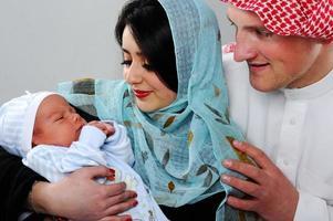 Arabisch moslimpaar met nieuwe baby thuis foto