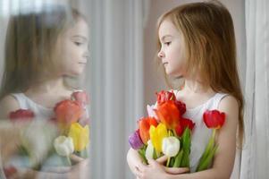 schattig klein meisje met tulpen bij het raam foto