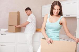 schattige man en vrouw verhuizen in een ander gebouw foto