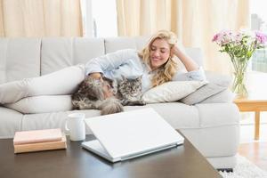 gelukkig blonde met huisdierenkat op bank foto