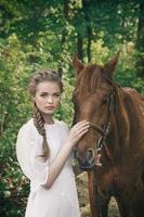 vrouw in vintage jurk aanraken van het gezicht van het paard foto