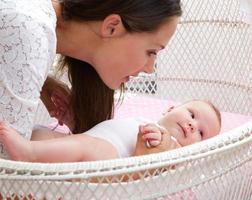aantrekkelijke vrouw met baby in wieg foto