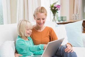 gelukkige moeder en dochter op de bank met laptop foto
