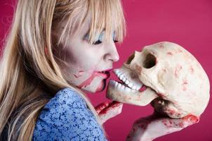 zombie Alice staat op het punt de schedel te kussen. foto