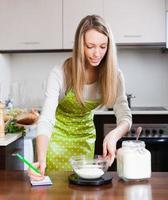 blonde vrouw met een gewicht van de vloer op de keukenweegschaal foto