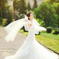 gelukkige brunette bruid ronddraaien met sluier foto