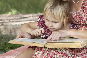 meisje ziet iets in boeken met moeder