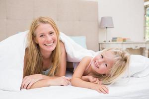 schattig klein meisje en moeder op bed foto