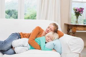 gelukkige moeder en dochter slapen op de bank foto