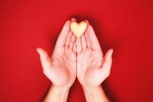 twee handen, die een klein houten hartje geniaal vasthouden foto