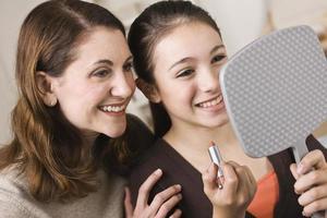 glimlachende moeder en dochter die spiegel onderzoeken foto