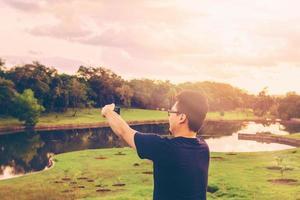 Japanse man die een selfie in het park neemt. foto