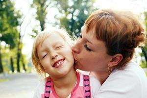 tedere moeder kuste haar dochtertje. foto