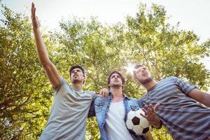 gelukkige vrienden in het park met voetbal foto