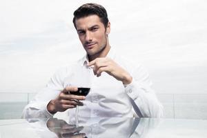 zelfverzekerde man met een glas wijn foto