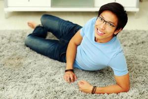 lachende Aziatische man liggend op de vloer