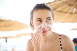mooie vrouw smeert gezicht met zonnebrandcrème foto
