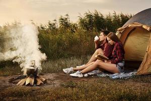jong stel door vuur op camping foto