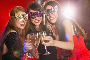 vrienden in maskerademaskers roosteren met champagne foto