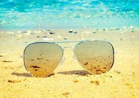 zonnebril op het zand foto