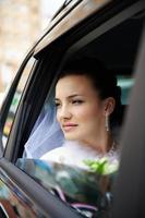 gelukkige bruid in een trouwauto