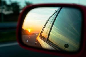 zonsondergang reflectie in de achteruitkijkspiegel