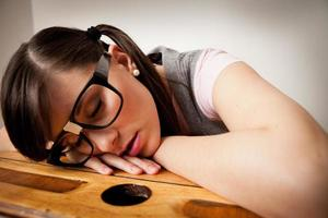 verveelde, nerdy jonge vrouw student slapen op schoolbank foto