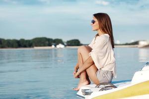 boot vrouw glimlachend gelukkig kijken naar de zee foto