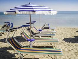 ligbedden en parasols op het strand foto